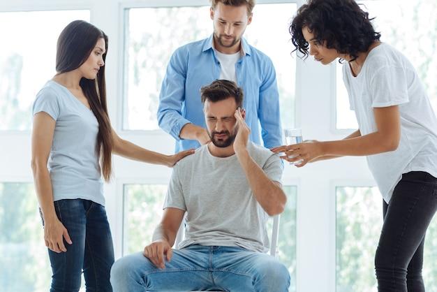 Triste homme barbu sans joie tenant sa tempe et souffrant du mal de tête tout en étant entouré d'amis