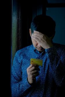 Triste homme confus et stressé détenant des cartes de crédit.