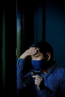 Triste homme confus et stressé tenant des cartes de crédit avec un masque facial.