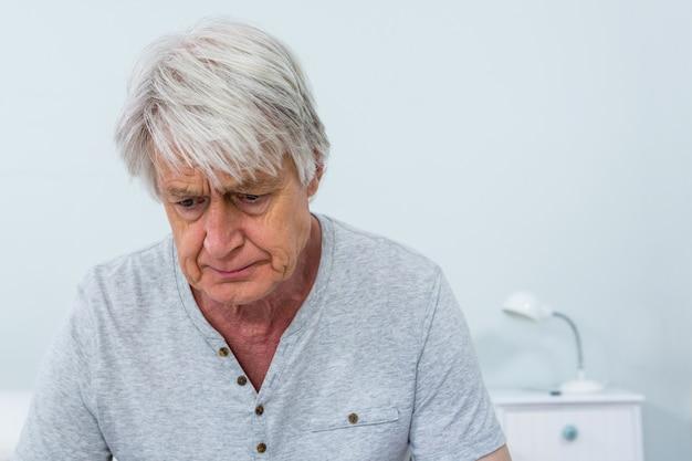 Triste homme senior assis à la maison