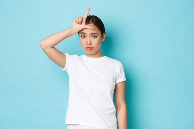 Triste et incertain en elle-même fille asiatique portant un t-shirt blanc décontracté, bouder et regarder glomy sur la concurrence perdue, montrant le geste de perdant sur le front, debout mur bleu