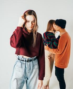 Triste jeune adolescente sur fond de couple d'amoureux, isolé. th