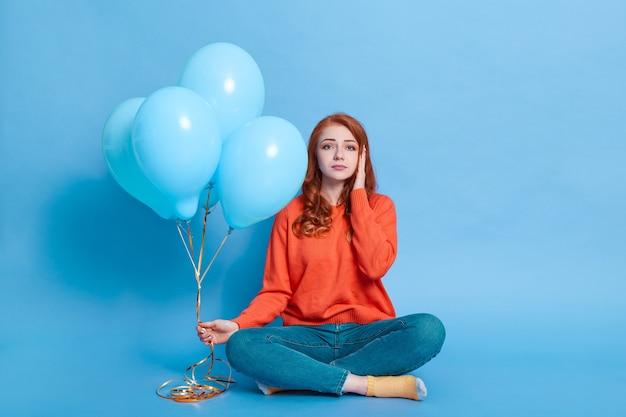 Triste jeune adulte assis sur le sol avec les jambes croisées tenant un bouquet de ballons à la main, regarde à l'avant