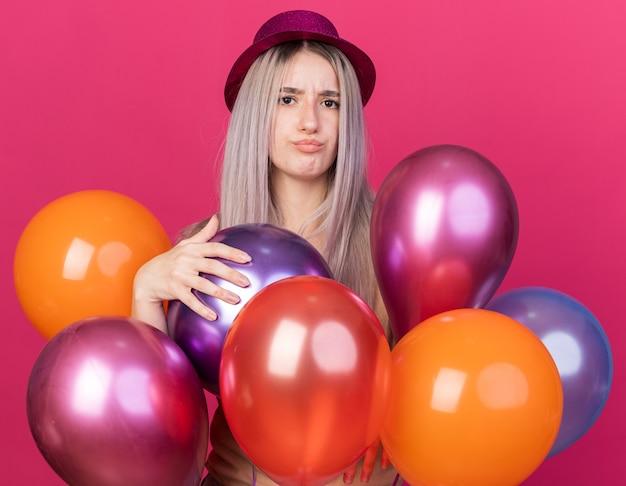 Triste jeune belle fille portant un chapeau de fête avec des appareils dentaires debout derrière des ballons