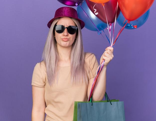 Triste jeune belle fille portant un chapeau de fête avec des lunettes tenant des ballons avec un sac-cadeau