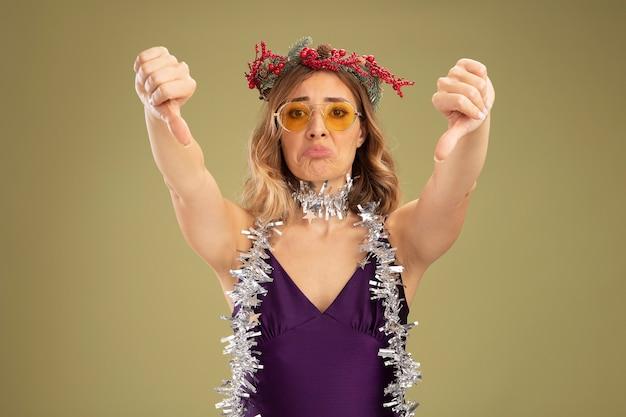 Triste jeune belle fille portant une robe violette et des lunettes avec une couronne et une guirlande sur le cou montrant les pouces vers le bas isolé sur fond vert olive