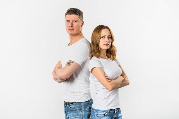 Triste jeune couple debout dos à dos isolé sur fond blanc