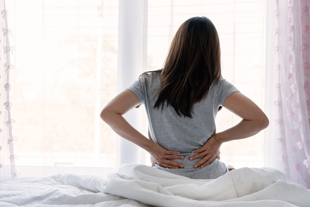 Triste jeune femme asiatique touchant le dos ressentir des maux de dos inconfort du matin faible douleur musculaire aux reins lombaires assis sur le lit après un mauvais sommeil se réveiller sur un matelas inconfortable en se pliant. concept de femme stretch