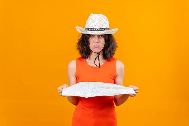 Une triste jeune femme aux cheveux courts dans une chemise orange portant un chapeau de soleil tenant une carte à la caméra étonnamment