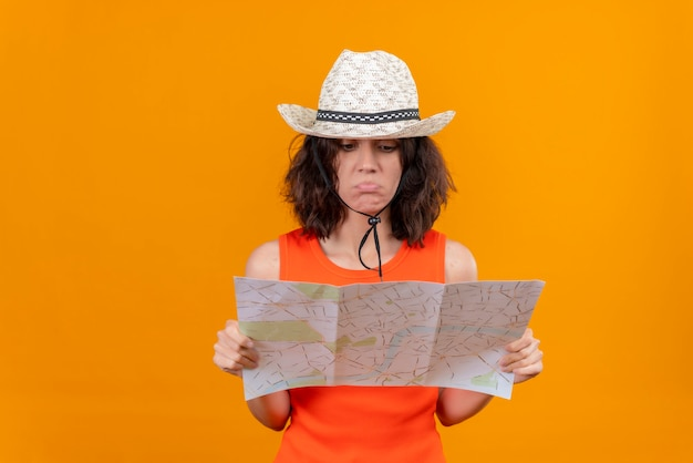 Une triste jeune femme aux cheveux courts dans une chemise orange portant un chapeau de soleil tenant une carte et en la regardant