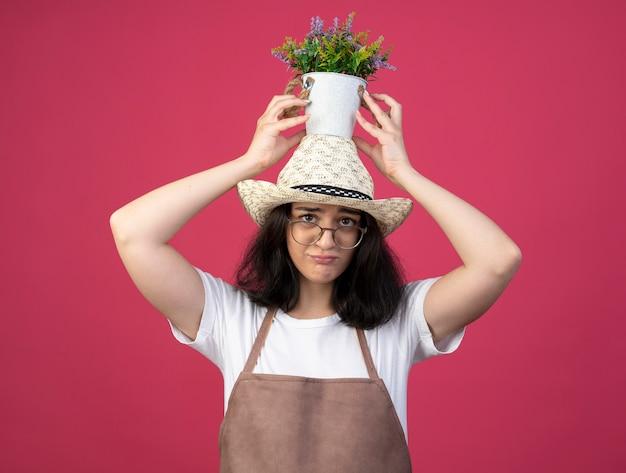 Triste jeune femme brune jardinière dans des lunettes optiques et en uniforme portant chapeau de jardinage détient pot de fleurs sur la tête isolé sur mur rose