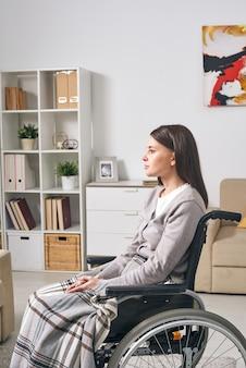 Triste jeune femme brune pensive assise sous une couverture en fauteuil roulant tout en passant du temps seul à la maison