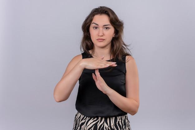 Triste jeune femme portant un maillot noir montre le geste de délai d'attente sur le mur blanc