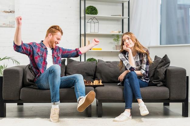 Triste jeune femme regardant son petit ami danser dans la joie après avoir remporté le jeu d'échecs