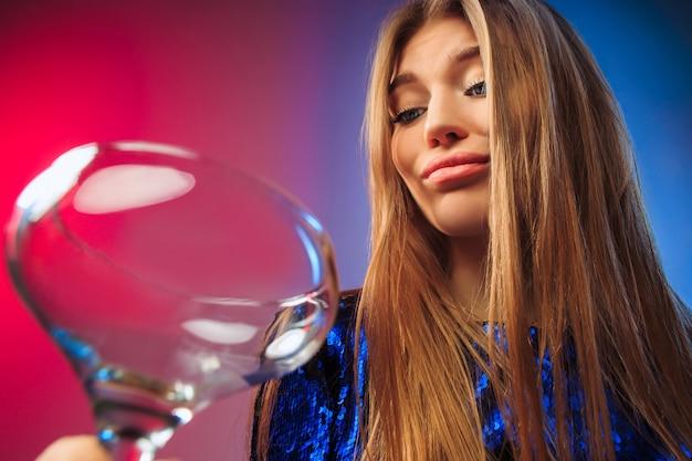 La triste jeune femme en tenue de fête posant avec un verre de vin.