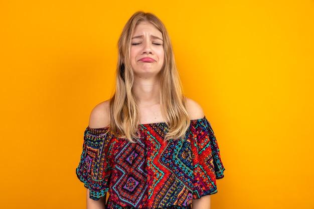 Triste jeune fille blonde slave debout avec les yeux fermés