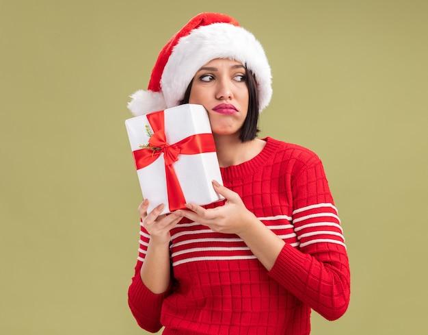 Triste jeune fille portant bonnet de noel tenant un paquet cadeau touchant le visage avec elle à côté isolé sur fond vert olive avec espace copie