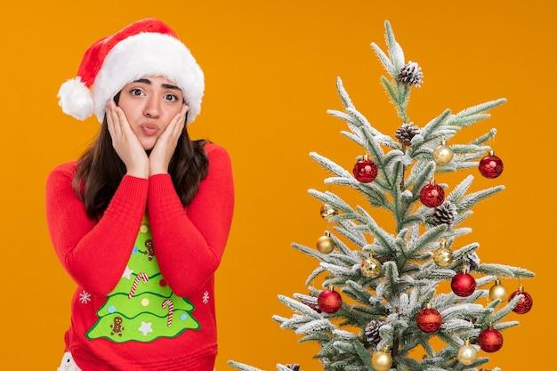 Triste jeune fille de race blanche avec bonnet de noel met les mains sur le visage debout à côté de l'arbre de noël isolé sur fond orange avec copie espace