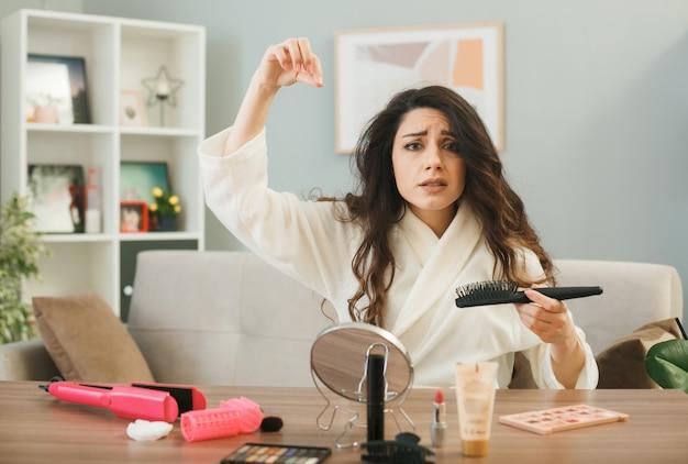 Triste jeune fille tenant un peigne assis à table avec des outils de maquillage dans le salon