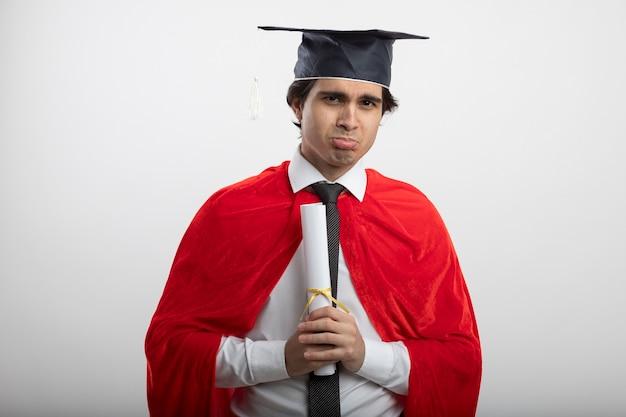 Triste jeune gars de super-héros regardant la caméra portant une cravate et un diplôme de diplômé hat holding