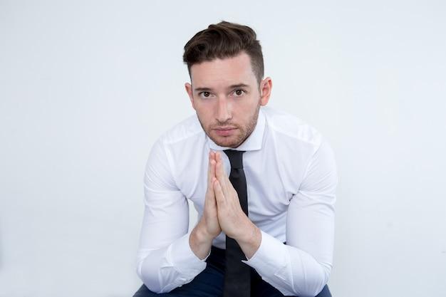 Triste jeune homme d'affaires priant pour le succès