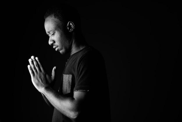 Triste jeune homme africain priant en noir et blanc