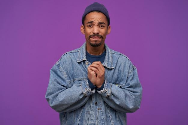 Triste jeune homme aux cheveux noirs barbu attrayant à la recherche inquiétante et en pliant les mains levées, fronçant les sourcils en se tenant debout sur le mur violet