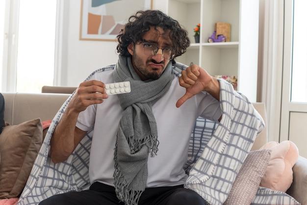 Triste jeune homme caucasien malade dans des lunettes optiques enveloppées dans un plaid avec une écharpe autour du cou tenant un blister de médicaments et un pouce vers le bas assis sur un canapé dans le salon