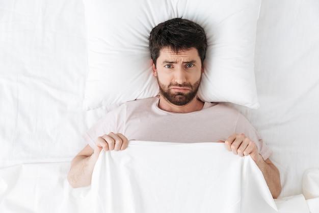 Triste jeune homme le matin sous une couverture au lit se trouve