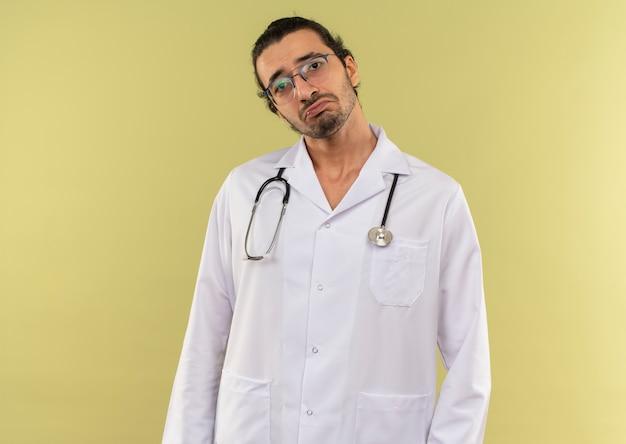 Triste jeune homme médecin avec des lunettes optiques portant une robe blanche avec stéthoscope sur mur vert isolé avec espace copie