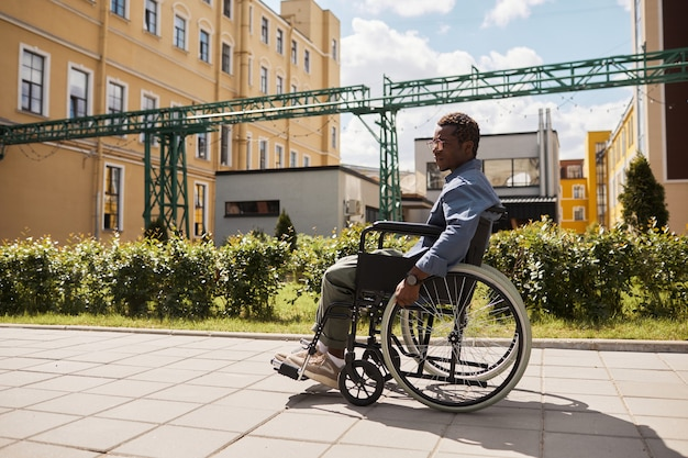 Triste jeune homme noir handicapé pensif dans des verres à l'aide d'un fauteuil roulant tout en marchant seul dans la rue