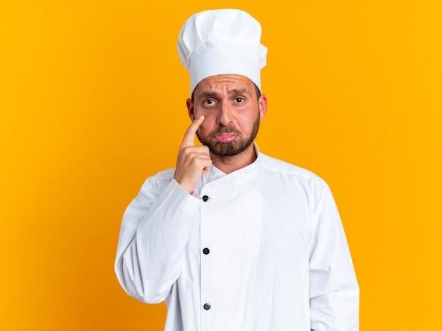 Triste jeune homme de race blanche cuisinier en uniforme de chef et casquette regardant la caméra en pinçant les lèvres tirant vers le bas la paupière inférieure isolée sur le mur orange