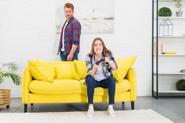 Triste jeune homme regardant une femme souriante profitant du jeu vidéo à la maison