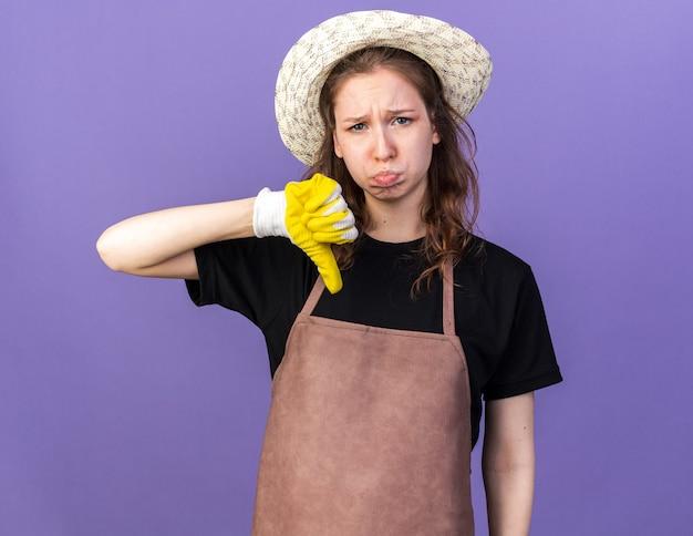 Triste jeune jardinière portant un chapeau de jardinage avec des gants montrant le pouce vers le bas