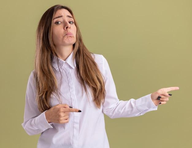 Triste jeune jolie fille caucasienne pointe à côté avec deux mains isolées sur un mur vert olive avec espace de copie