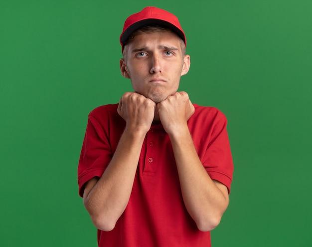 Triste jeune livreur blond met les poings sur le menton isolé sur mur vert avec espace de copie