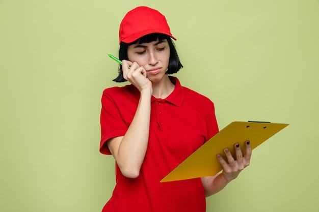 Triste jeune livreuse caucasienne tenant et regardant le presse-papiers