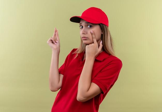 Triste jeune livreuse portant l'uniforme rouge et une casquette montrant le geste de pointe isolé vert