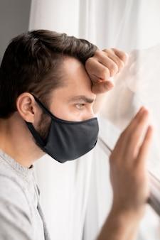 Triste jeune patient de sexe masculin en masque facial regardant par la fenêtre et s'appuyant dessus à l'hôpital