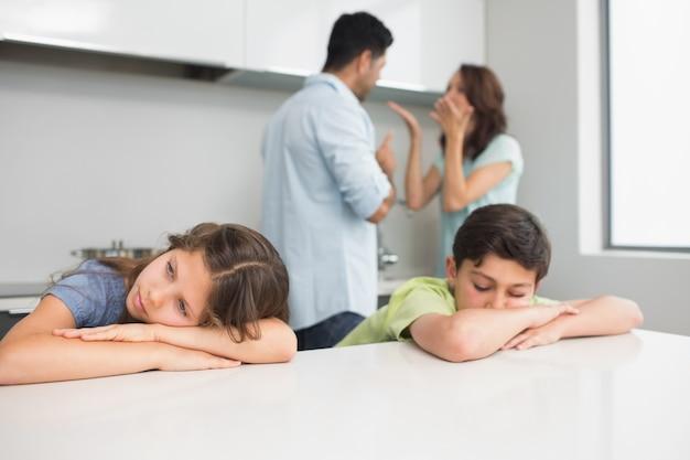 Triste jeunes enfants pendant que les parents se querellent dans la cuisine