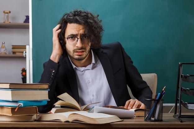 Triste mettant la main sur la tête d'un enseignant portant des lunettes assis à table avec des outils scolaires en classe