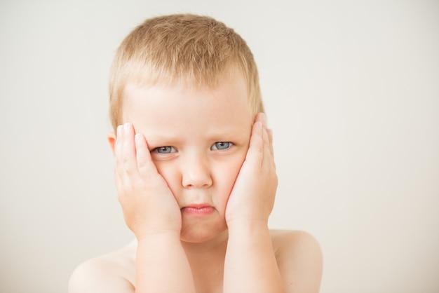 Triste mignon petit garçon debout avec les mains sur les joues