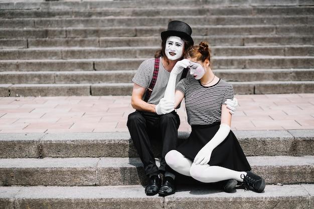 Triste mime couple assis sur l'escalier