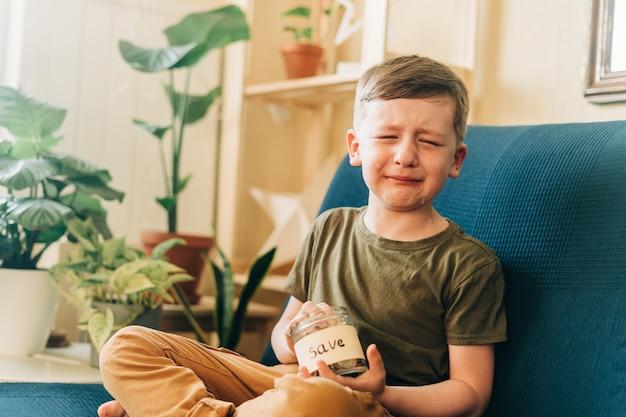 Triste petit enfant qui pleure garçon mettant des pièces de pile dans un bocal en verre avec économiser le don de l'étiquette