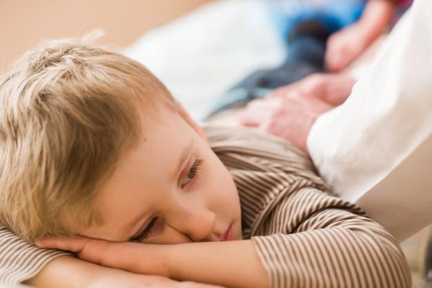 Triste petit garçon allongé au canapé