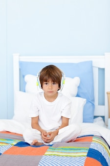 Triste petit garçon écoutant de la musique au lit