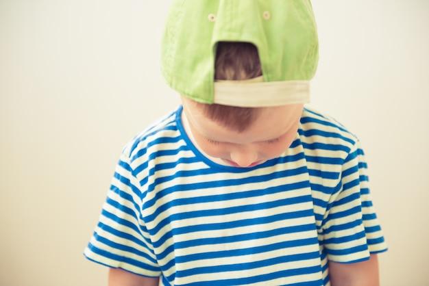 Triste petit garçon se tient la tête baissée