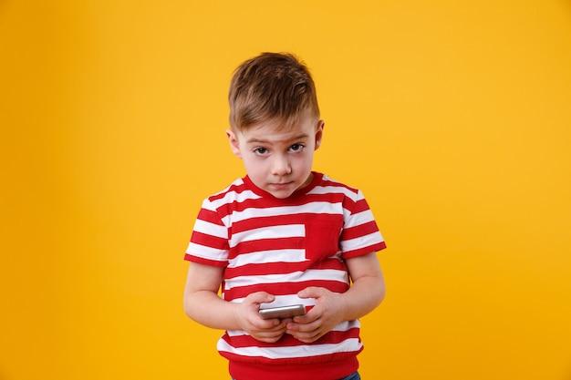 Triste petit garçon tenant un téléphone mobile