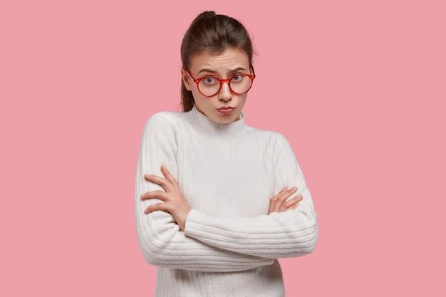 Triste petite amie malheureuse a une expression maussade, garde les bras croisés, est offensée par un mec, vêtue de vêtements blancs