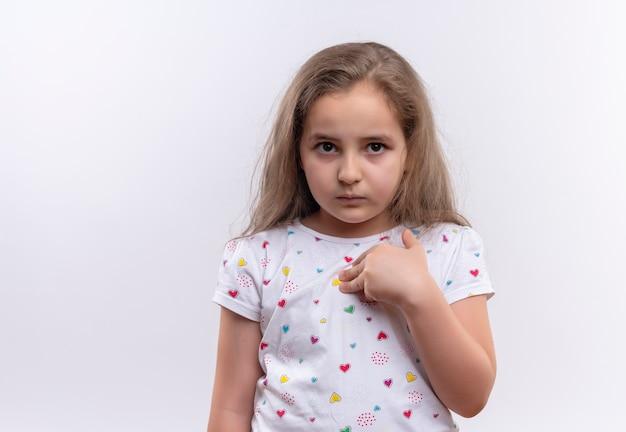 Triste petite écolière portant un t-shirt blanc se pointe sur fond blanc isolé